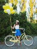 Stylish young female with a bicycle in park. Girl enjoying a day on bike Stock Photo