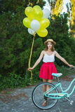 Stylish young female on a bicycle in park. Girl enjoying a day on bike Stock Photos