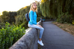 Stylish young girl with a backpack sitting Royalty Free Stock Photography