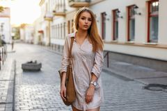 Stylish young girl with bag shopping in the city at sunset.  Stock Photo