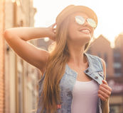 Stylish young girl. Beautiful stylish young girl in casual clothes, hat and sun glasses is looking at the sun and smiling while walking outdoors Stock Photography
