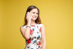 Stylish young girl in bright light dress talking by phone stock image