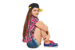 Stylish young girl in a cap, a shirt and denim shorts. Street style teenager, lifestyle, isolated on white background Royalty Free Stock Images