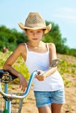 Stylish young girl in casual wear posing with bike Stock Photos