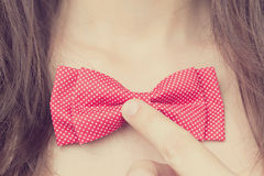 Stylish young girl holding a bow-tie near the neck Stock Image