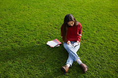Stylish young girl holding some book in the park Stock Photography