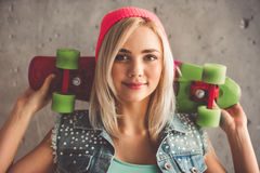 Stylish young girl. In jean clothes is holding a skateboard, looking at camera and smiling, on concrete wall background Royalty Free Stock Images
