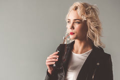 Stylish young girl. In leather jacket and sun glasses is drinking soda water, on gray background Stock Photos