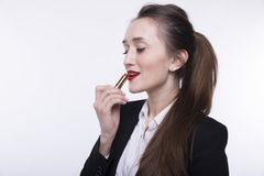 Stylish young girl with long hair in a dark business suit paints her lips with red lipstick stock photo