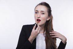 Stylish young girl with long hair in a dark business suit paints her lips with red lipstick stock photos