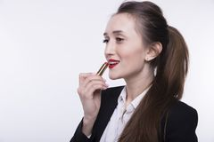 Stylish young girl with long hair in a dark business suit paints her lips with red lipstick royalty free stock image