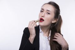 Stylish young girl with long hair in a dark business suit paints her lips with red lipstick royalty free stock photos
