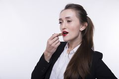 Stylish young girl with long hair in a dark business suit paints her lips with red lipstick stock images