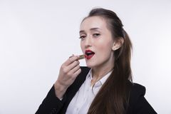 Stylish young girl with long hair in a dark business suit paints her lips with red lipstick stock photography