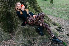 Stylish young girl lying on the tree roots in spring park. Stock Image