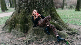 Stylish young girl lying on the tree roots in spring park. Royalty Free Stock Images