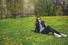 Stylish young girl in a plaid shirt and sunglasses sitting on green grass in the spring Stock Photography