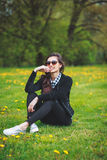 Stylish young girl in a plaid shirt and sunglasses sitting on green grass in the spring Royalty Free Stock Photos