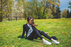 Stylish young girl in a plaid shirt and sunglasses sitting on green grass in the spring Stock Images
