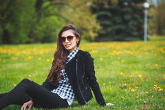 Stylish young girl in a plaid shirt and sunglasses sitting on green grass in the spring Royalty Free Stock Images