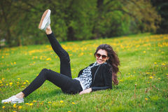 Stylish young girl in a plaid shirt and sunglasses sitting on green grass in the spring Royalty Free Stock Image