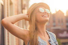 Stylish young girl. Portrait of beautiful stylish young girl in casual clothes, hat and sun glasses looking at the sun and smiling while walking outdoors Royalty Free Stock Photo