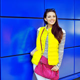 Stylish young girl posing near blue wall Royalty Free Stock Image