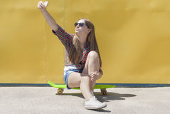 Stylish young girl sitting on a skateboard Royalty Free Stock Image
