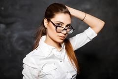 Stylish young girl student in a white blouse and glasses on a da. Rk background. hot teacher woman Royalty Free Stock Images