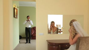 Stylish young groom and bride getting ready for their big day in their apartments stock video footage