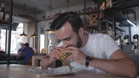 Stylish young guy with a beard bites a burger sitting at a table in a cafe. man eating a burger. 4k. 4k video. 60 fps.  stock footage