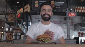 Stylish young guy with a beard sits in a cafe at a table with a plate with a burger, laughs and jokes. man eating a burger. 4k. 4k. Video. 60 fps stock video
