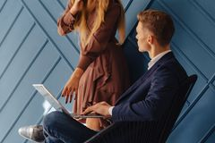 Stylish young guy with laptop and girl with phone together, young businessman, freelancer work, aqua background royalty free stock photos