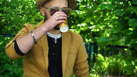 Stylish young guy in the Park drinking coffee stock video