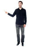 Stylish young guy pointing away Stock Images