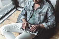 Stylish young guy is using his modern device Royalty Free Stock Photography