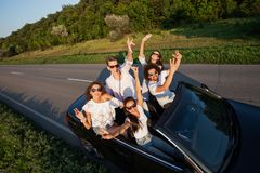 Stylish young guys are sitting, holding hands up and smiling in a black cabriolet on the country road on a sunny day. stock photo