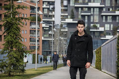 Stylish Young Handsome Man in Black Coat Standing in City. Center Street with Skyscraper Behind Him, Looking to the Camera Royalty Free Stock Photography