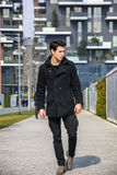 Stylish Young Handsome Man in Black Coat Standing in City Center. Street with Skyscraper Behind Him, Looking to the Right Stock Image