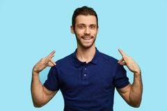 Stylish young handsome man is smiling and pointing at his blue t-shirt stock photos
