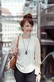 Stylish Young Happy Woman Taking an Escalator. Portrait of a Stylish Young Happy Woman with Brown Leather Shoulder Bag, Taking an Escalator While Smiling Into Stock Photography