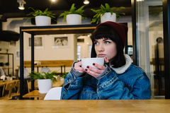 Stylish young hipster girl sitting in a cafe drinking coffee and looking in the window. And dreaming Stock Images