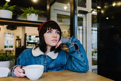 Stylish young hipster girl sitting in a cafe drinking coffee and looking in the window. And dreaming Stock Photo