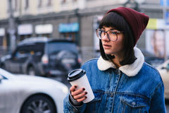 Stylish young hipster girl walks in the city and drinking coffee on the background of cars. Stylish young girl hipster glasses and jeans jacket walking in the Royalty Free Stock Photos