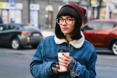 Stylish young hipster girl walks in the city and drinking coffee on the background of cars. Stylish young girl hipster glasses and jeans jacket walking in the Stock Image