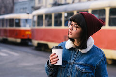 Stylish young hipster girl walks in the city and drinking coffee on the background of the tram. Stylish young girl hipster glasses and jeans jacket walking in Stock Photography