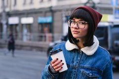 Stylish young hipster girl walks in the city and drinking coffee. Stylish young girl hipster glasses and jeans jacket walking in the city and drinking coffee on Royalty Free Stock Photos
