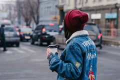 Stylish young hipster girl walks in the city and drinking coffee. Stylish young girl hipster glasses and jeans jacket walking in the city and drinking coffee on Stock Photo