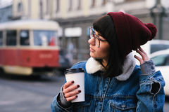 Stylish young hipster girl walks in the city and drinking coffee and straightens hair. Stylish young girl hipster glasses and jeans jacket walking in the city Stock Image