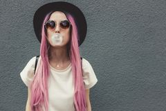 Stylish young hipster woman with long pink hair blowing a bubble with bubble gum. royalty free stock photography